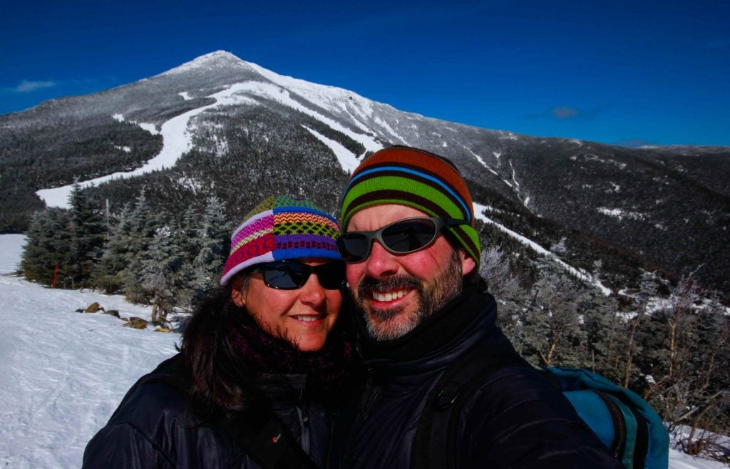 Shari and Hutch huddle close for an icy winter selfie in front of a mountain peak