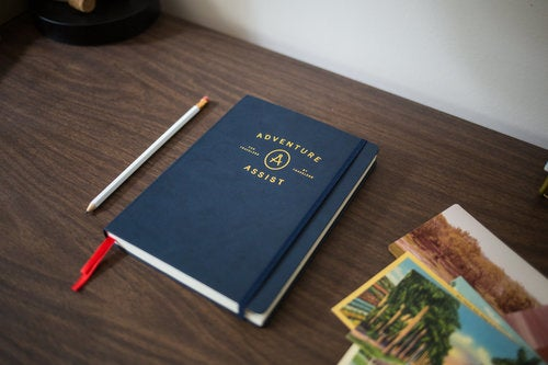 navy adventure assist camping journal on a wood desk