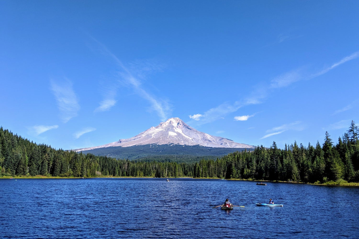 mount hood on a sunny day in oregon with trillium lake below and people kayaking along it