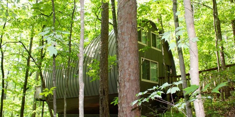 A Unicoi State Park barrel cabin sits in the shaded forest next to Unicoi Lake