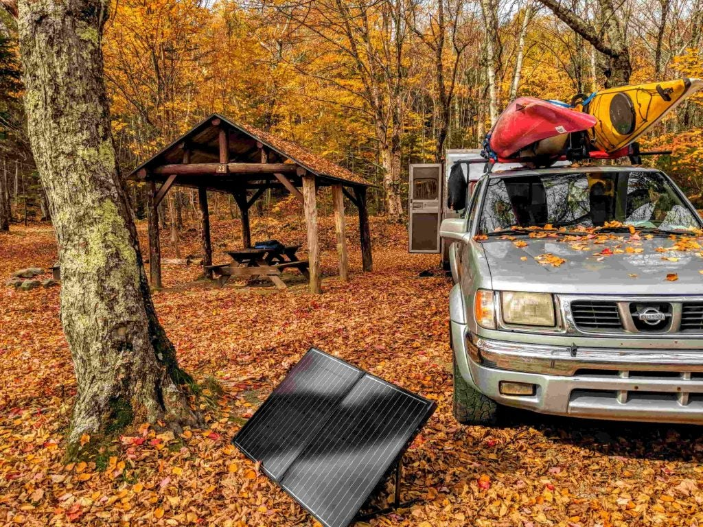 shari and hutch's solar panel set up at a campground in the fall