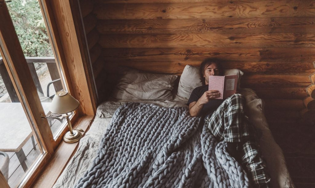 man lounges in bed in a cabin reading a pink book