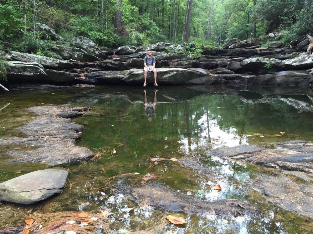 Man sitting on rock above creek