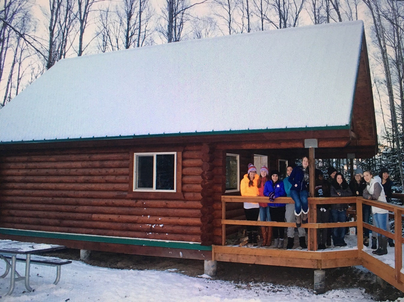 a group of campers pose for a photo on the front porch of their snowy cabin in bird creek, ak