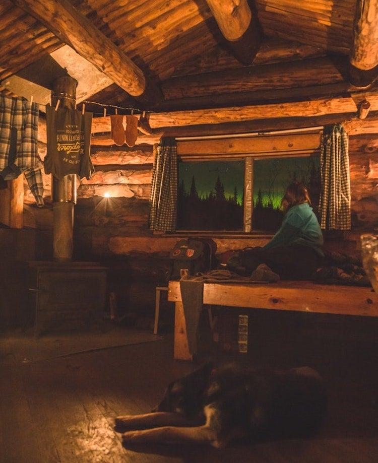 camper rests inside her warmly lit, cozy cabin in alaska as the northern lights flicker outside