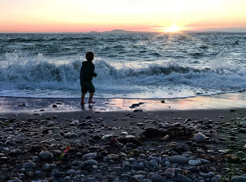 Child plays among waves at sunset on San Juan Islands