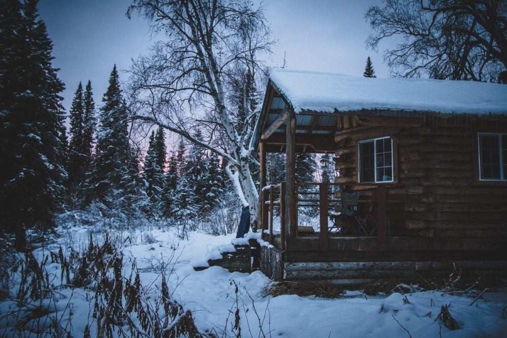 side view of a snowy cabin at dusk