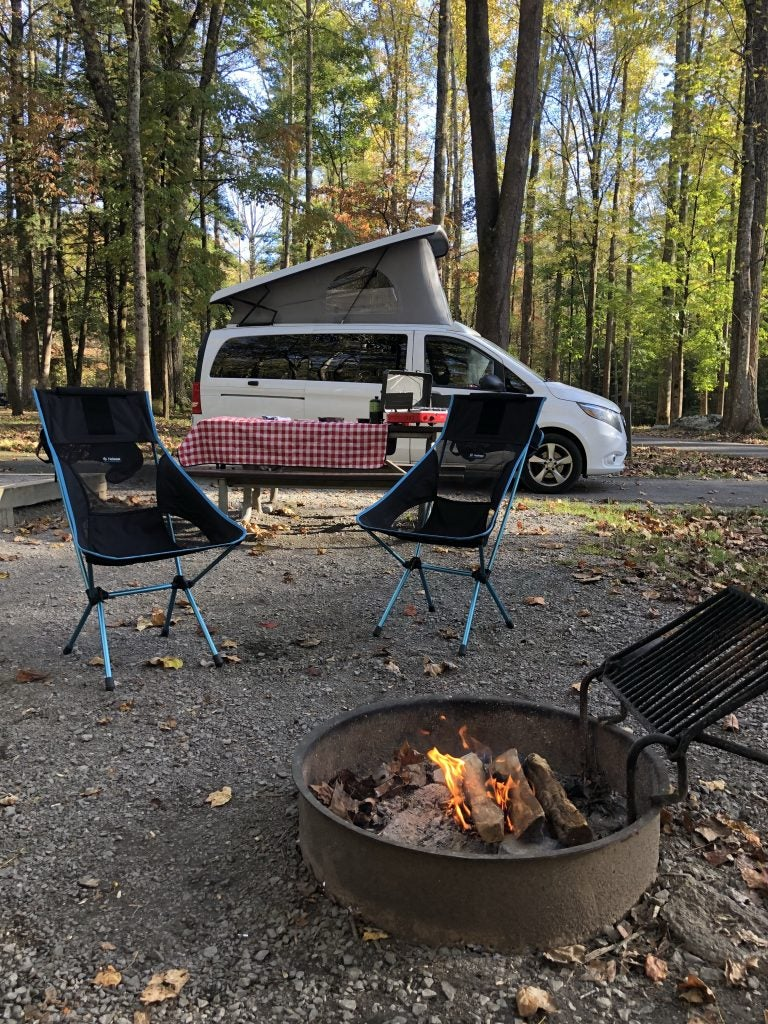 Campsite set up with burning firepit and chairs