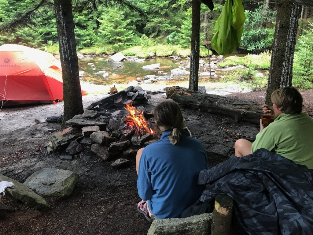 Two people sit around a fire at a campground near a creek
