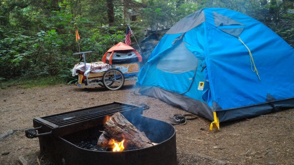 Blue tent and campfire with bike buggy in the background