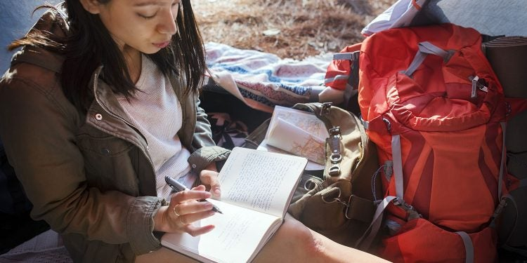 woman writing in her camping journal in her tent