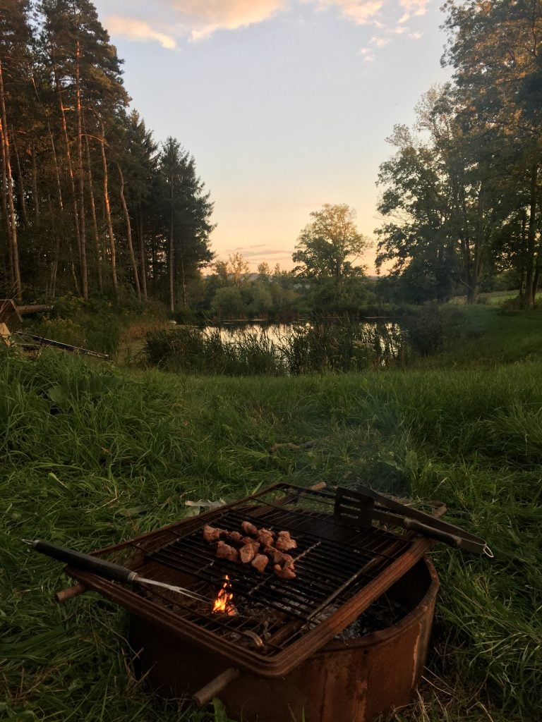 grilling over a campfire with lake in background during sunset