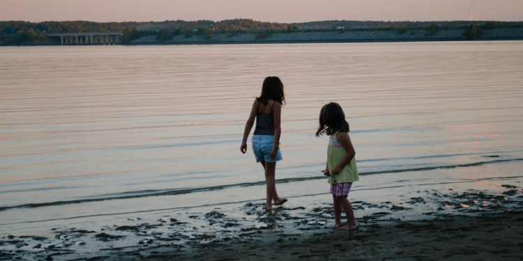 silhouette of two girls playing in the water at sunset on a jordan lake camping trip