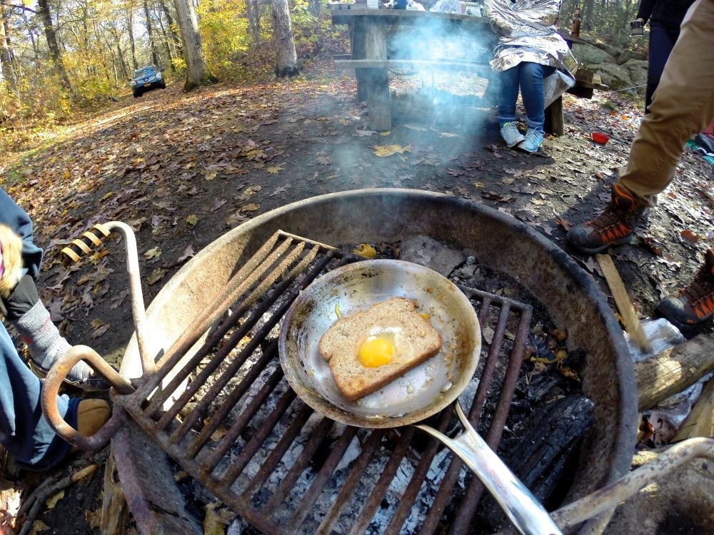 fisheye lens view campers frying an egg on toast over a campfire
