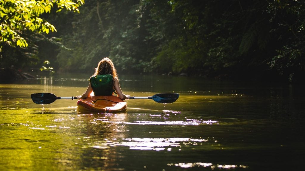 view from behind of a woman kayaking in a nc waterway