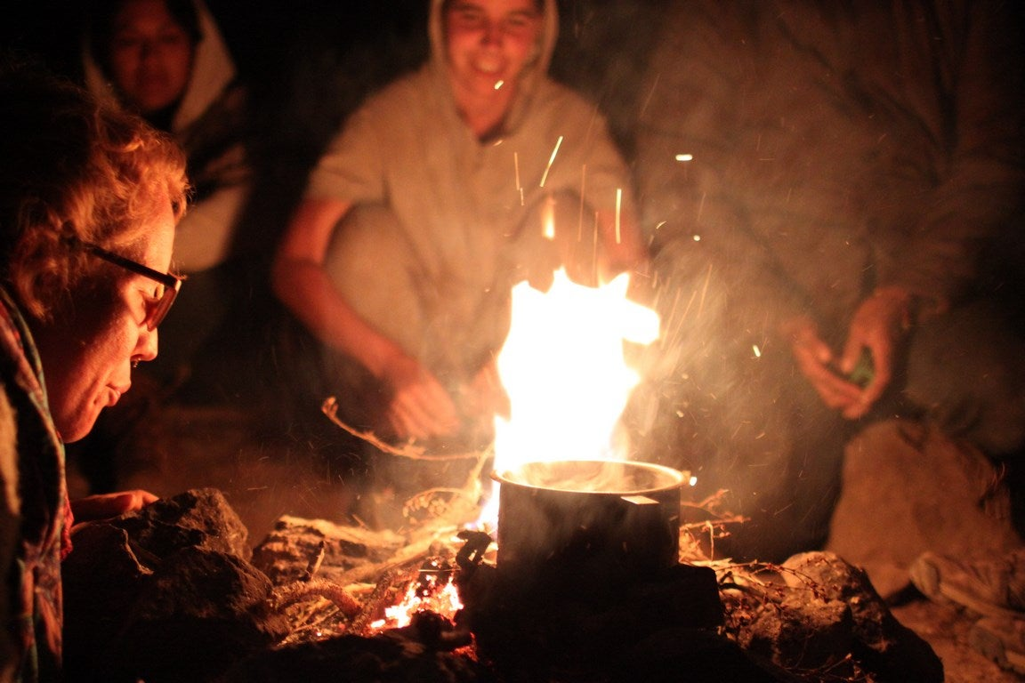 friends smiling around a campfire