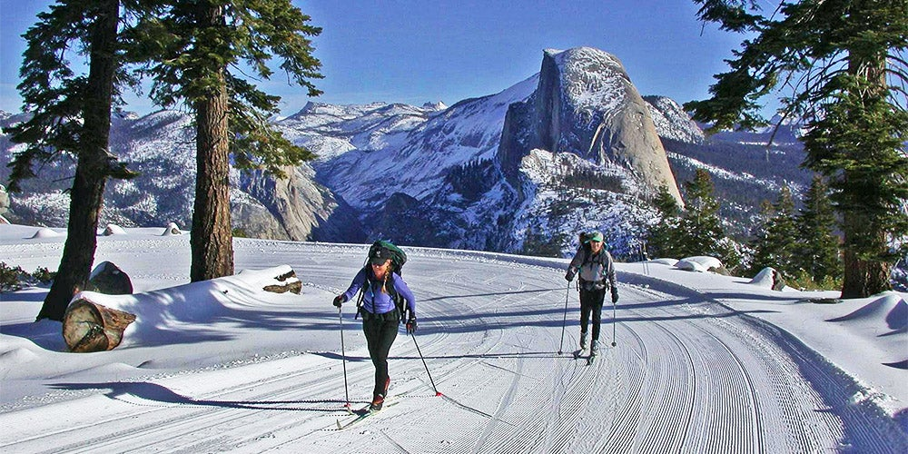 two cross country skiers on badger pass trail with half dome in background