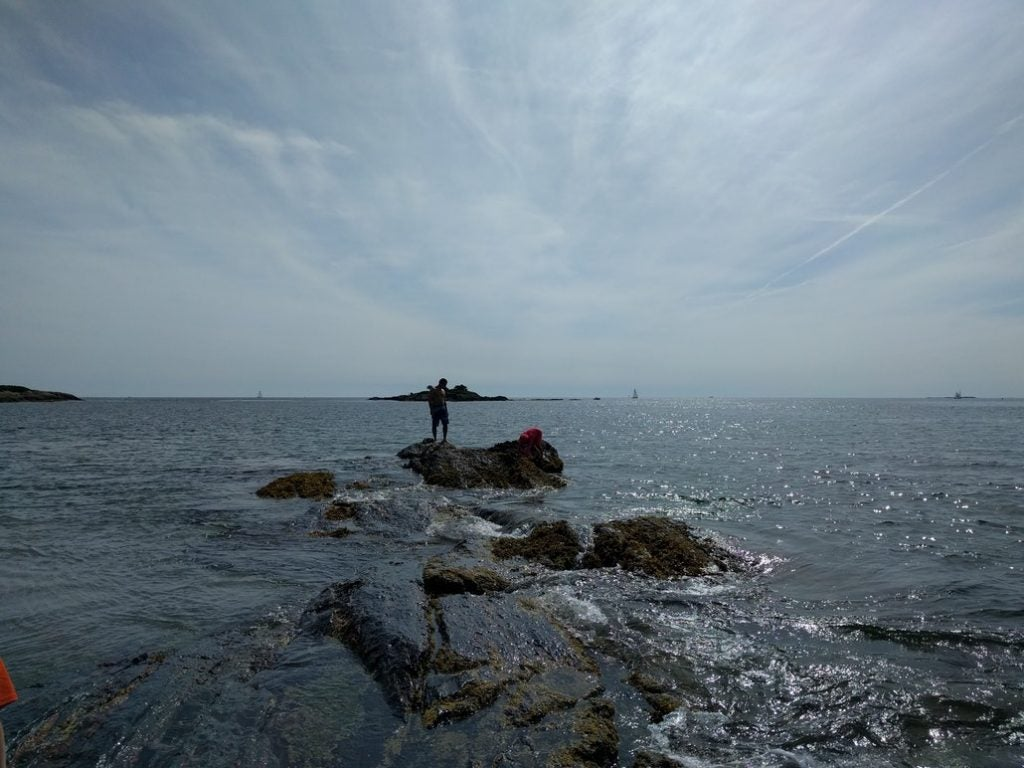 A man stands on a rocky outcropping in the Atlandic ocean on the coast of Maine's Hermit Island