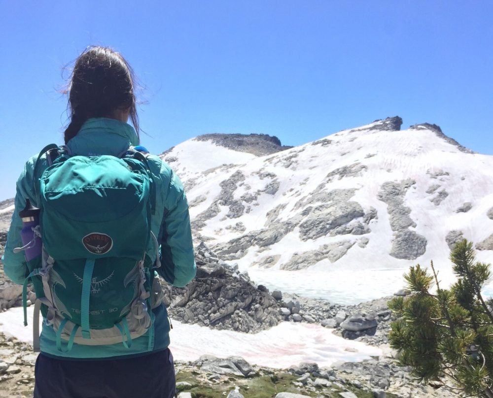 back view of hiker wearing teal backpack and looking at snowy mountain