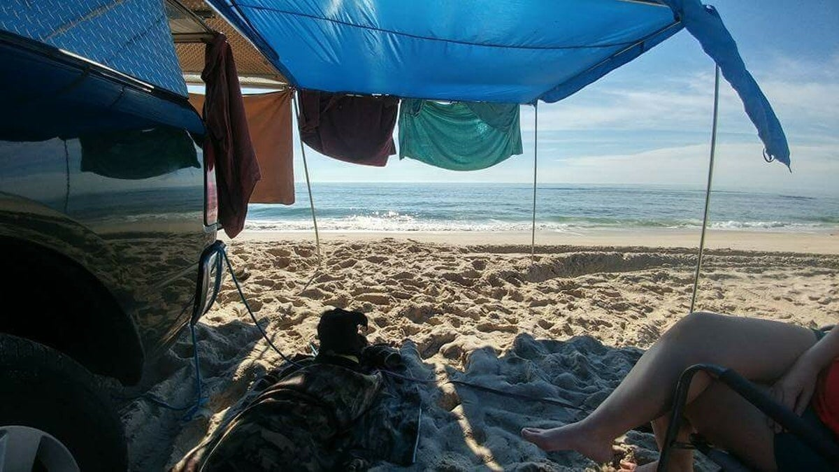 car campers relax on the beach at a drive-in beach campsite