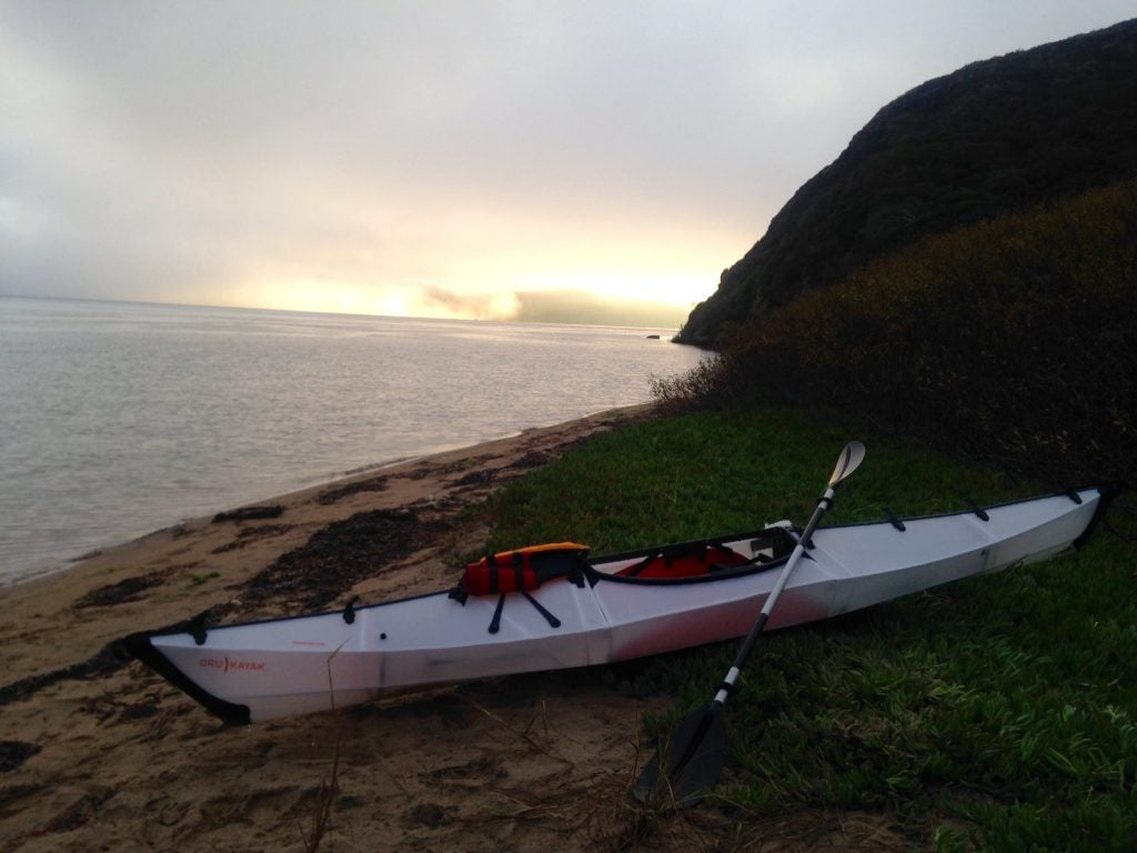 Kayak sits on shore ready to ride in the San Juan Islands