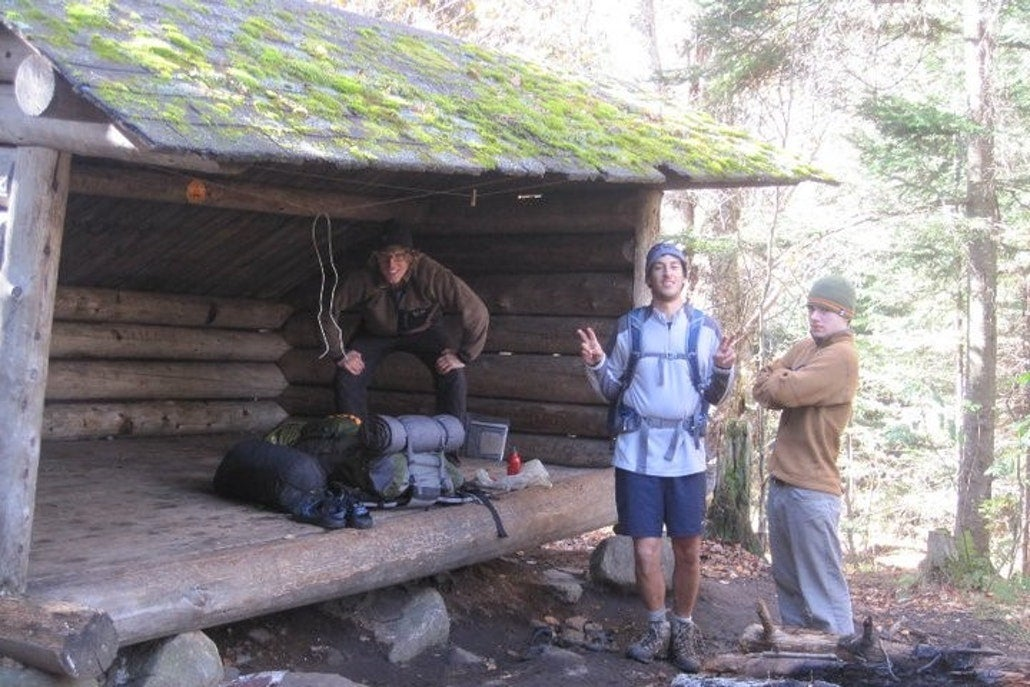 campers set up gear in a primitive lean -to shelter
