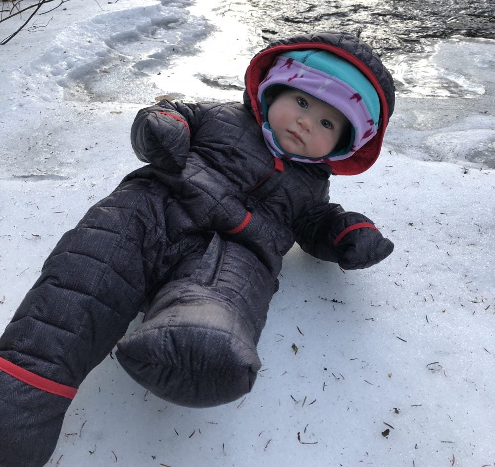 baby in black insulated bodysuit lounges on icy patch of ground