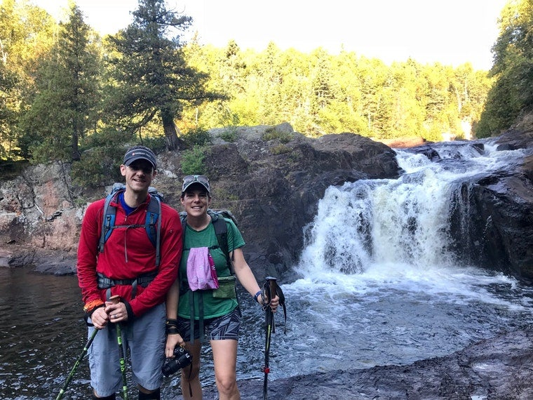 Two hikers with backpacks and poles in front of a waterfall.