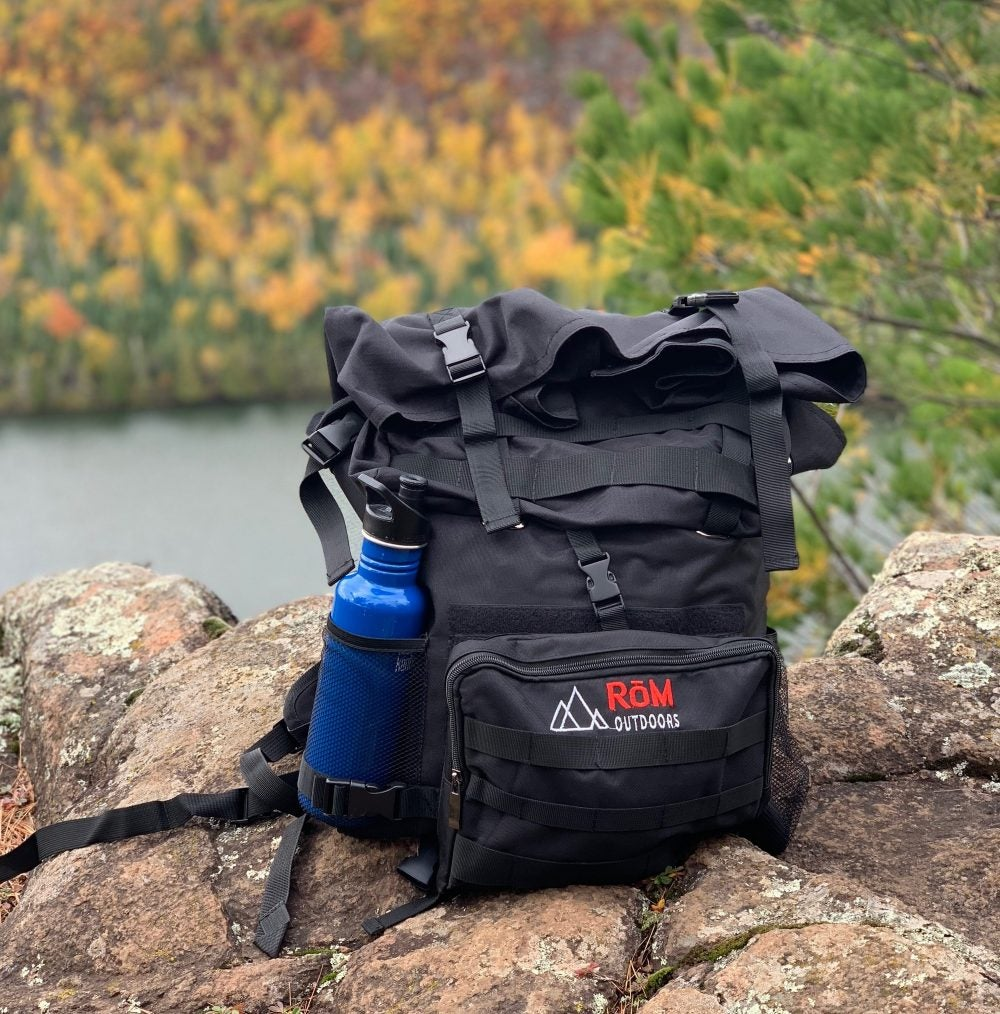 A RoM backpack rests nestled on a rocky ledge overlooking a calm river and autumn trees.