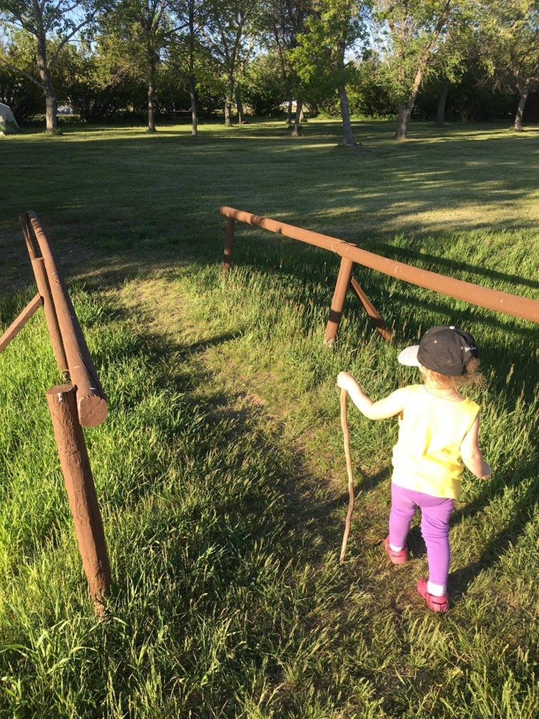 young girl with walking stick travels a grassy path in fort stevens state park