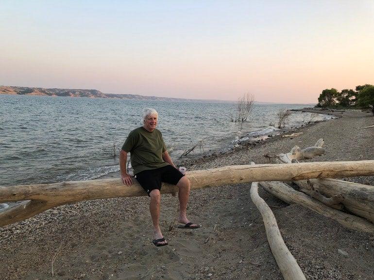 beachgoer enjoys a north dakota sunset from a driftwood log