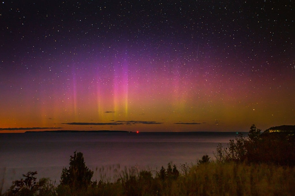 pink and purple northern lights over a michigan lake