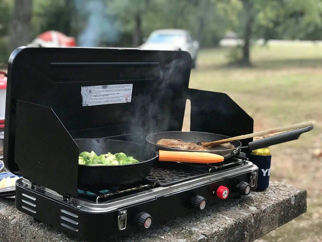 a tailgate grill heats up hot dogs and veggies