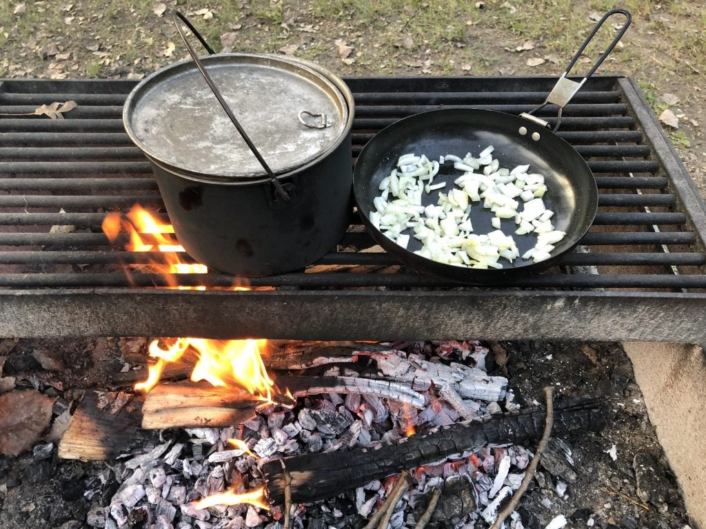 Cooking onions on stove on campfire for tailgate party