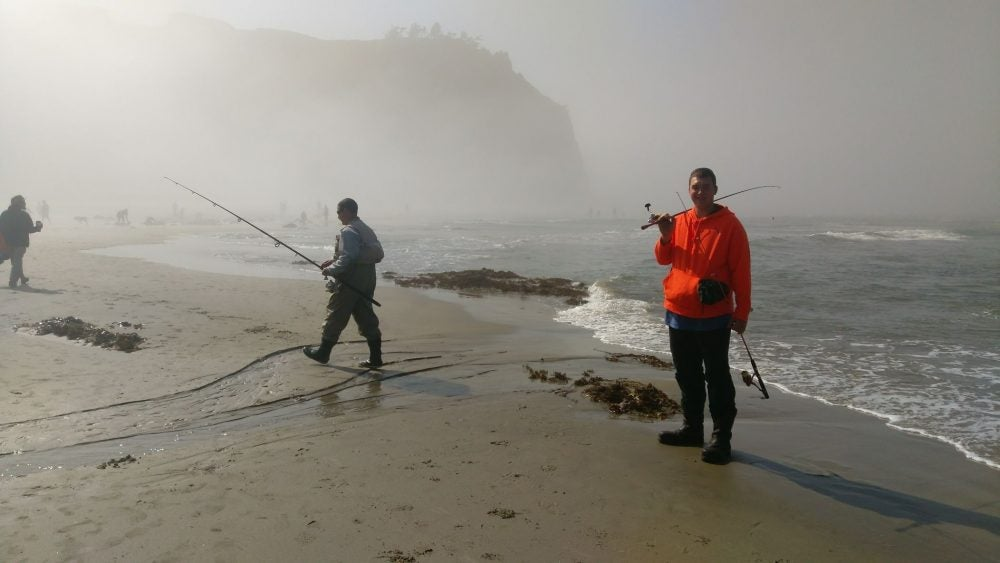 foggy ocean beach with fishermen