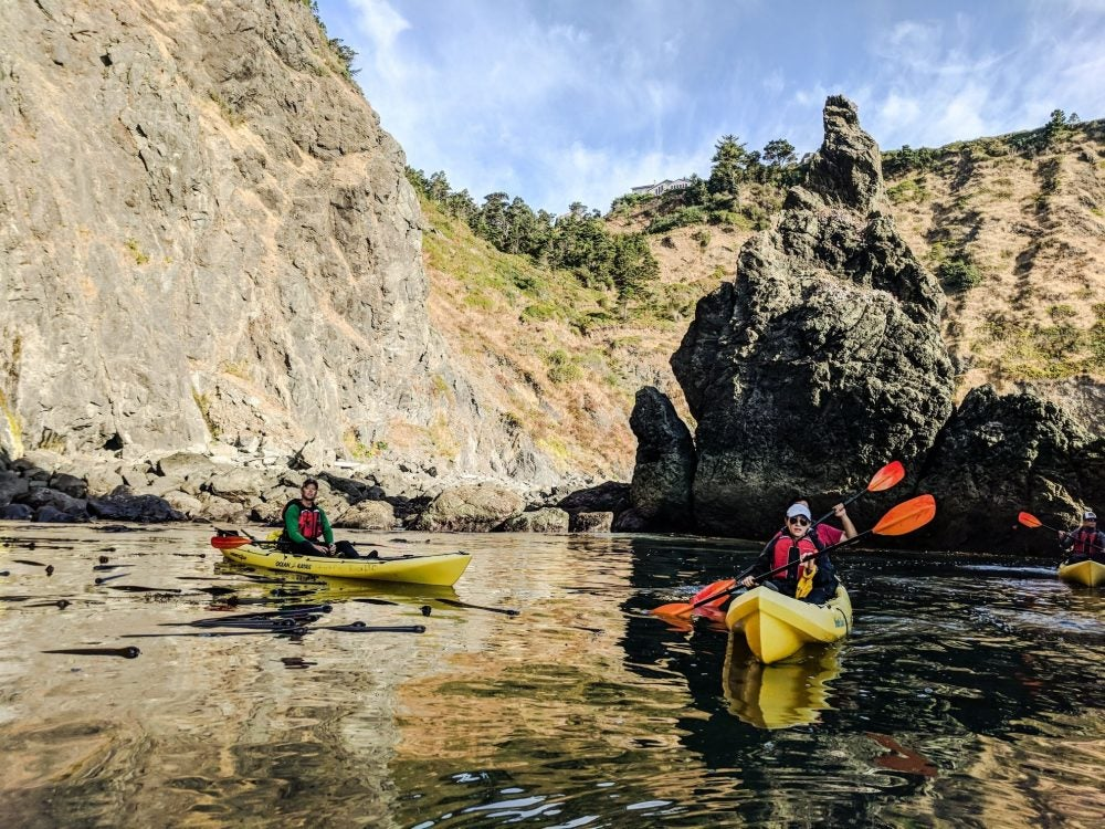kayakers at cape blanco in front of rocks