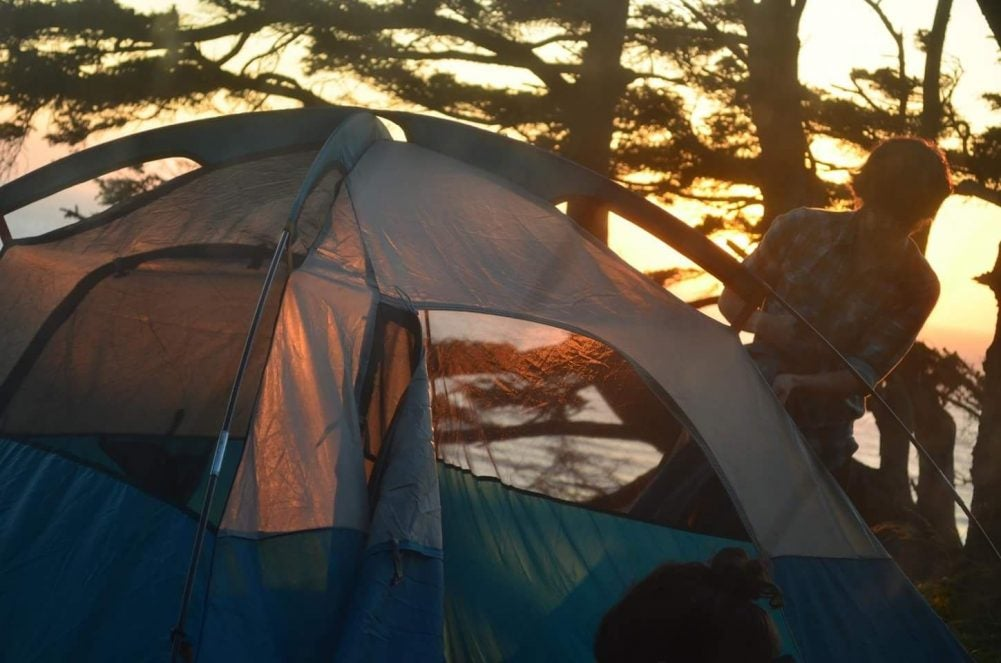 sunsets as camper sets up tent