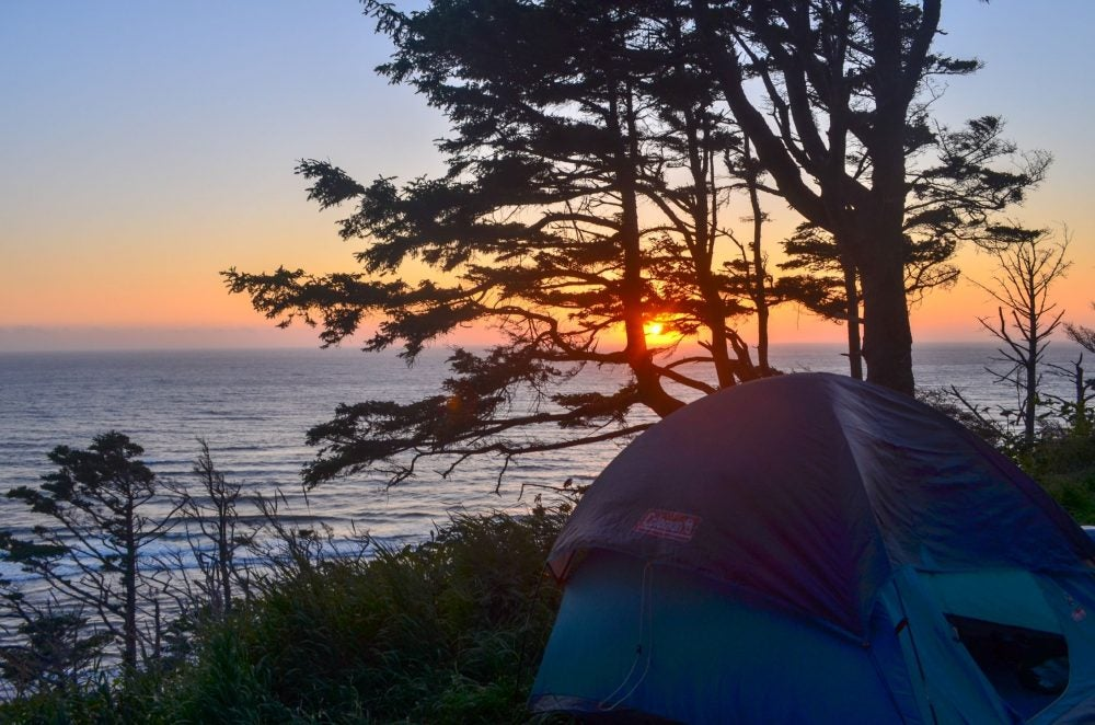 tent and trees in the foreground with ocean and sunset in the background