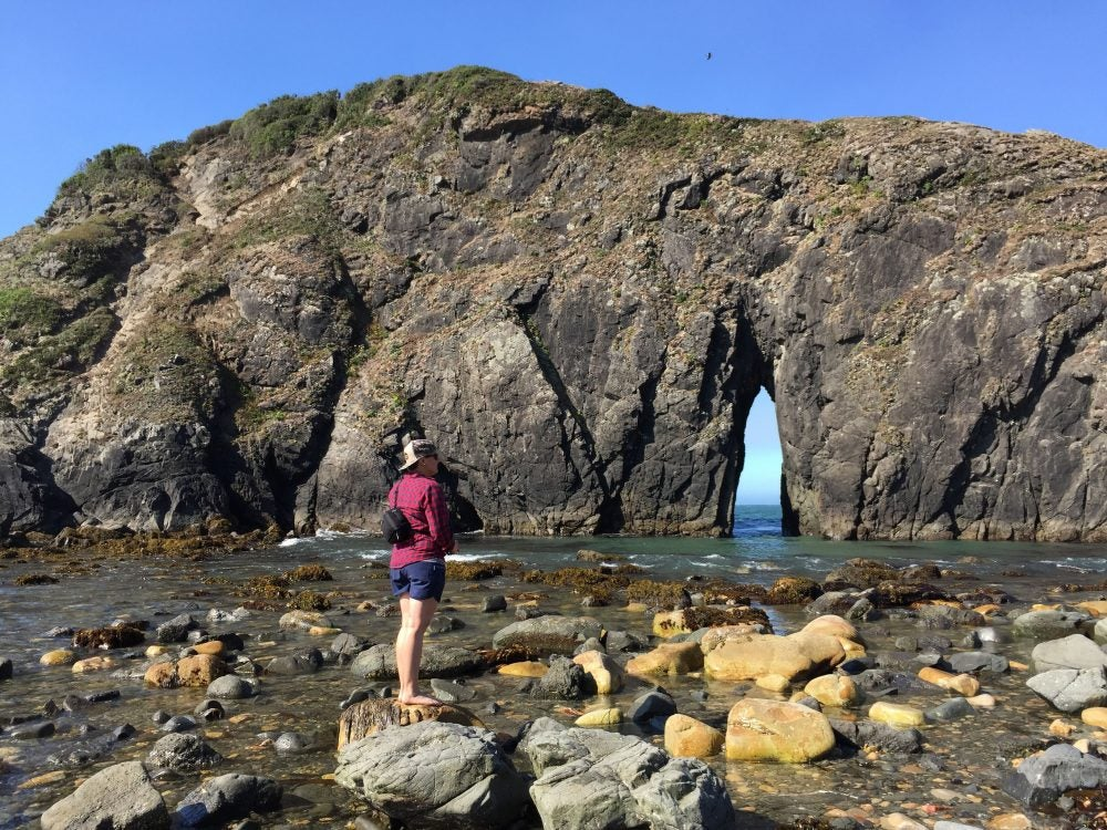 hikers stands on rocks looking towards natural arch at harris beach