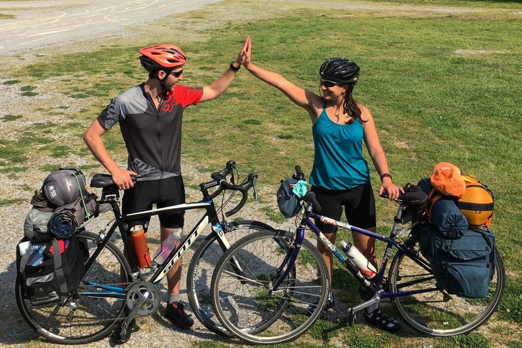 two bikers high-five on the trail