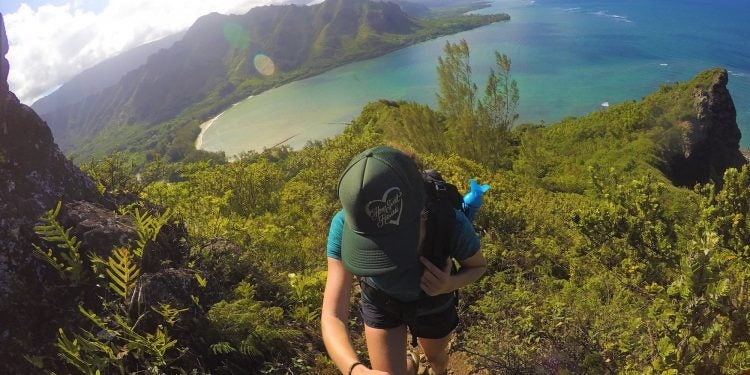 woman hiking Kahana Valley, lush green mountains over teal coastal waters