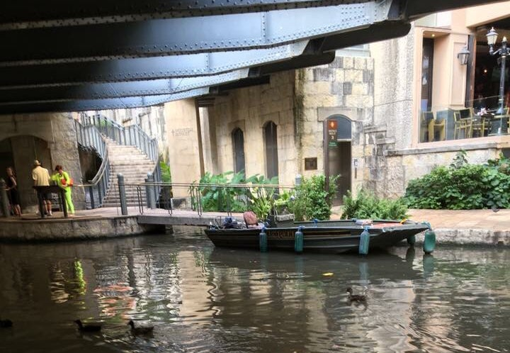 tin boat floats on the san antonio river below a bridge on the river walk