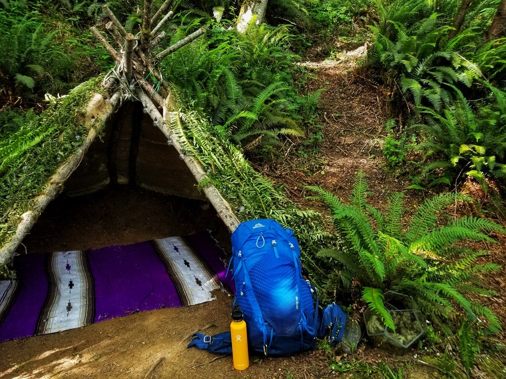 A primitive tent made from grass and sticks in the woods, with a backpack out front. backpacks are found on our primitive camping checklist