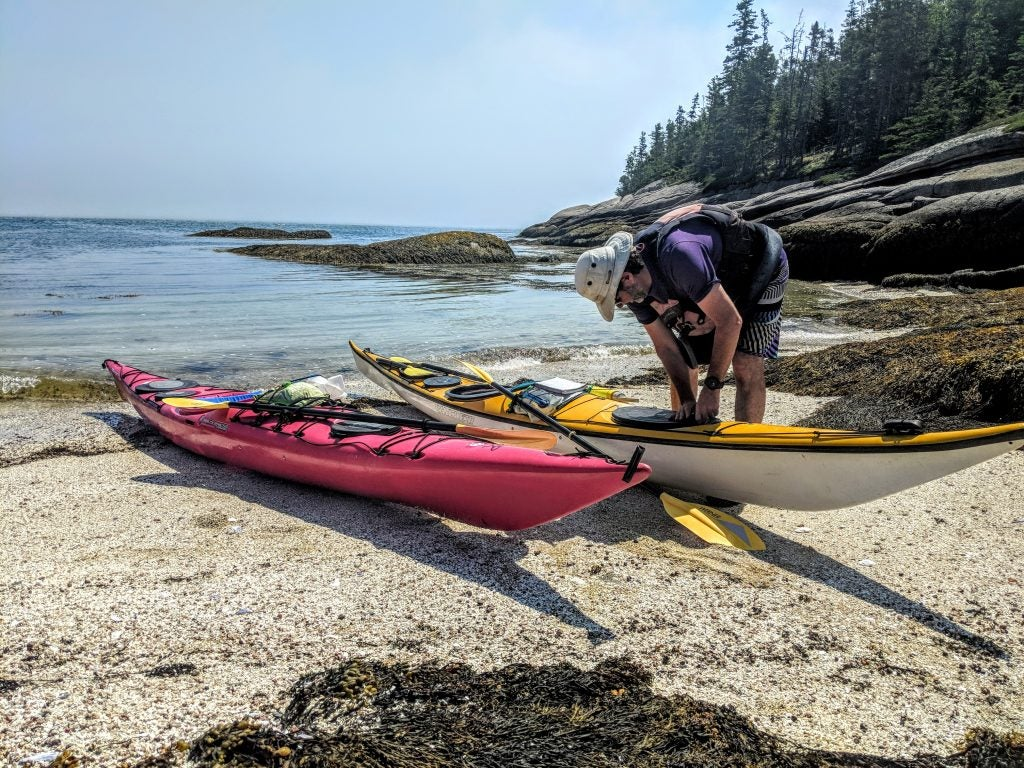 Kayaker works on his kayak on San Juan Island shoreline