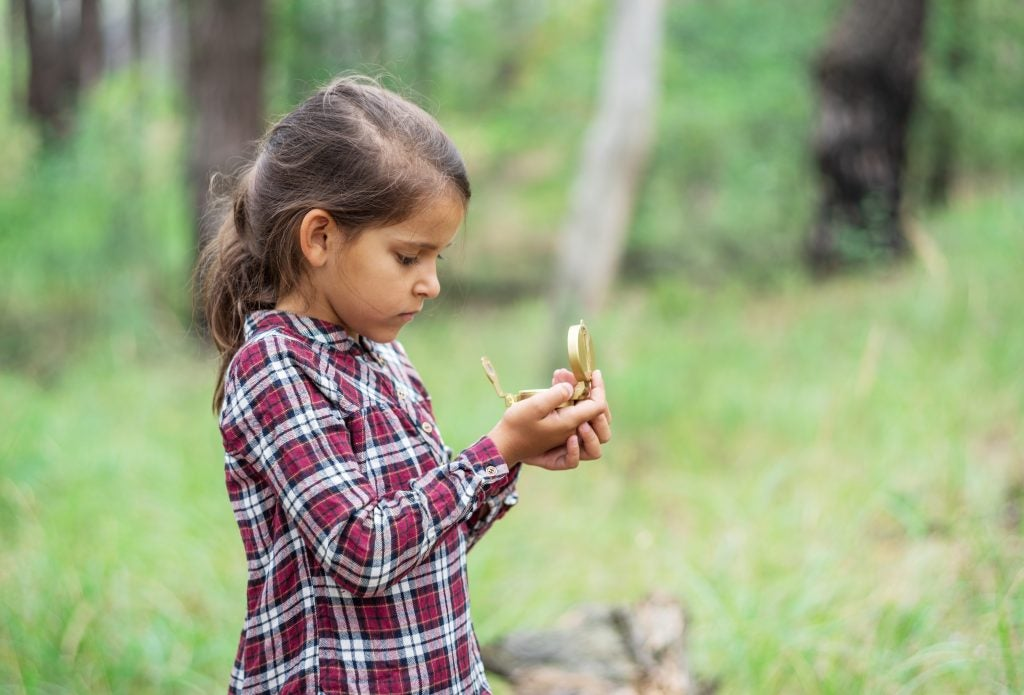 Young girl learning how to geocache with compass