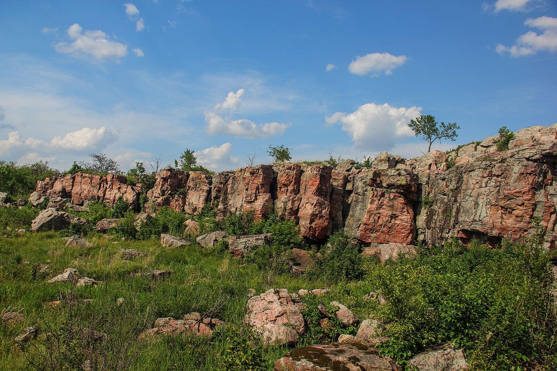 Cliffs in a grass field under a blue sky.