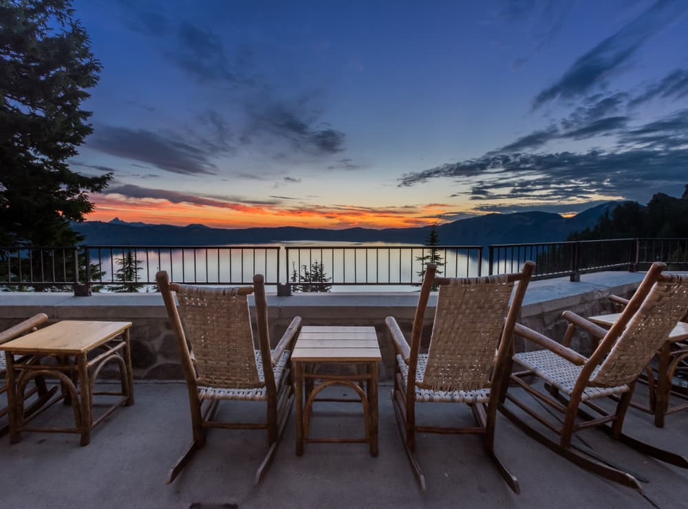 rocking chairs and table overlooking crater lake at sunset