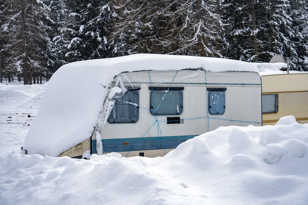 winterized rv with a tarp protecting it from a layer of snow