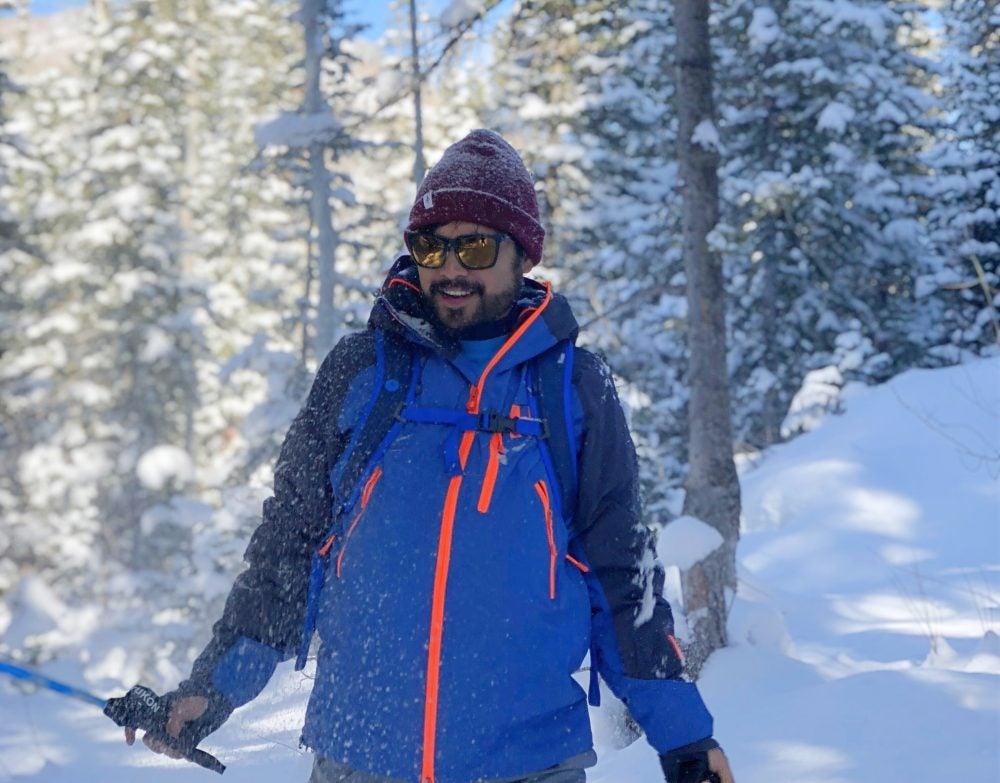 snowball flies through the air toward man in sunglasses and red beanie