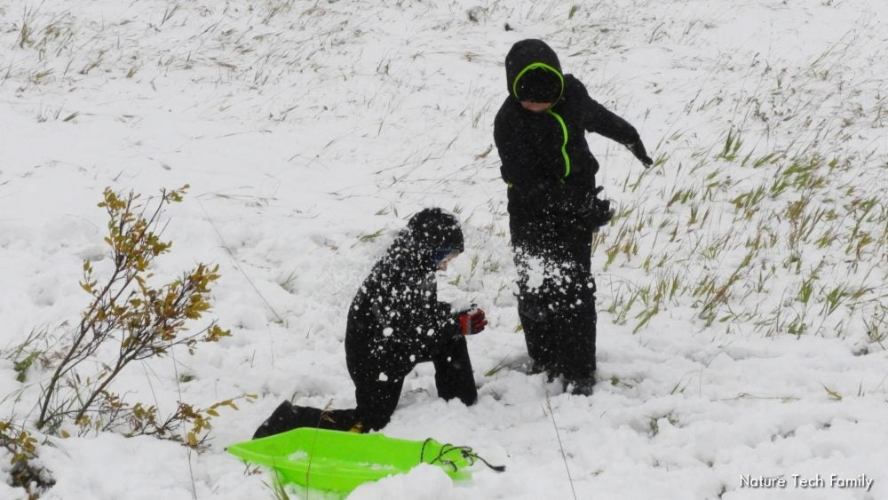 two kids sledding and playing in the snow